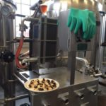 Brewery with stainless equipment plus plate of snacks,green rubber gloves hanging on pipe, glass of beer