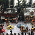 model of Victorian village with horse drawn sleigh snow buildings evergreens