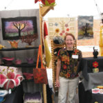 Woman with print blouse and beige slacks standing in front of booth displayed art pieces