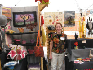 Woman with print blouse and beige slacks standing in ArtFest booth with her designs