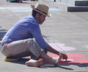 man in straw hat blue shirt tan pants sitting on pavement drawing at sidewalk chalk festival