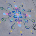Sidewalk chalk drawing with dark blue swirls and dots of blue pink yellow on gray sidewalk