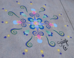 Sidewalk chalk drawing with swirls and dots of blue pink yellow