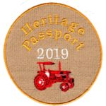 Beige circular cloth patch with Heritage Passport embroidered in gold letters 2019 in white and red tractor