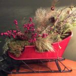 Arrangement of silvery evergreens and red berries in red sleigh on wood shelf