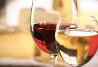closeup of white wine in glass with larger glass of red wine behind, blurred background