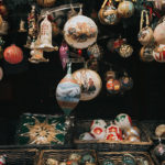 many antique Christmas ornaments of different shapes hanging over boxes of elaborate ornaments