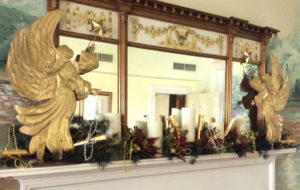two gold angels and evergreen garland on white mantel with mirror above