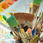 multicolor paint brushes of different sizes in beige pottery jar with artwork behind