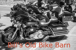 black and white motorcycles in a row on gray pavement Orange text: Bill's Old Bike Barn