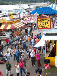 overhead shot of visitors gathered between vendor booths like Benton Cider Mill as they enjoy food at the Bloomsburg Fair