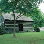 Green lawn with gray and white log Quaker meetinghouse built 1789 large tree shading it