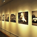Five black and white photographs displayed in a row on cream wall under track lighting