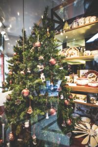 view through glass to Christmas tree with red ornaments and wood store shelves with pottery and wooden gifts