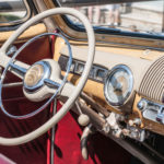 Closeup - beige and silver metal steering wheel and dashboard in antique car with red interior