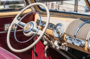 Old car interior with beige steering wheel & dashboard