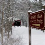 Burgundy and gold sign for Josiah hes Covered Bridge in foreground, snow covered trees and red bridge in background