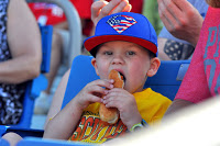 Danville young boy in blue Crosscutters cap and yellow shirt eating hot dog  held in both hands, crowd behind!