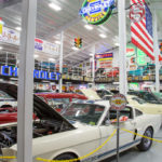 red and white antique cars with open hoods in foreground, many other cars behind in auto museum with neon signs hanging above