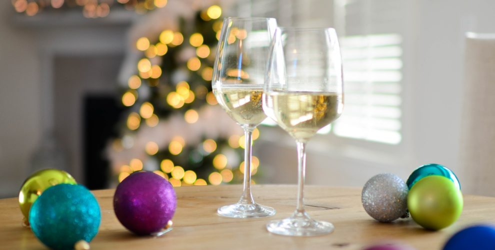 2 glasses white wine and Christmas balls on table with lighted Christmas tree and window with blinds behind