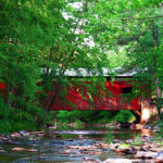 Esther Furnace Covered Bridge - red covered bridge over rocky stream surrounded by green-leafed trees