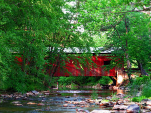 Esther Furnace Covered Bridge - red bridge over rocky stream surrounded by trees