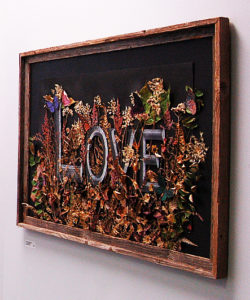 wooden framed art work with word L O V E against dark background with flowers