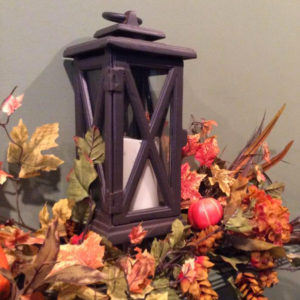 Fall leaves surrounding bronze lantern with pillar candle