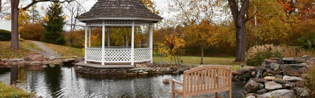 White gazebo by the pond with fall leaves in the background