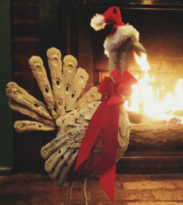 Turkey sculpture with red bow around neck and Santa hat in front of blazing fireplace