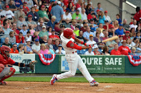 baseball player in white uniform with red sleeves and helmet hitting baseball with fans in stands behind Danville!