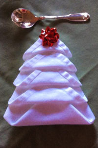 white napkin folded to look like a christmas tree with red bow at top
