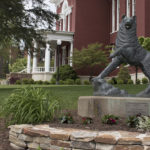 bronze statue of Husky in front of red brick campus building with white columns on portico