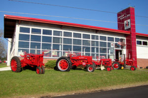 Three red tractors & International Harvester prototype dealership with façade of large multi-paned glass and red roof and tower displaying IH logo