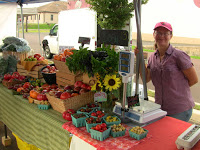 fresh fruits and vegetables on display to sell at farmers market with woman working behind the table