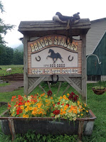 Sign for Brace's Stables with silhouette of horse and 2 horseshoes in center, shingle roof at top, red, orange flowers and green foliage in trough at bottom of sign