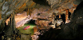 underground cavern with gray and brown stalactites and stalagmites surrounding green pool with red boat