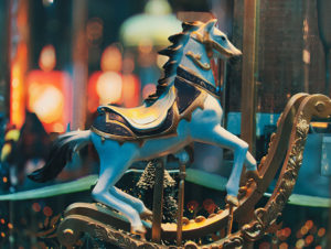 Antique blue carousel horse with gold rockers and black mane and tail with out-of-focus carousel in background