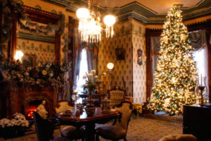 Victorian drawing room at Christmas with tree, table and chairs in front of fireplace decorated with greens