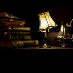 stack of old books, lighted antique lamp with tilted cream shade, silver pitcher on table in dark room