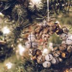 closeup of wreath of mini gold and white jingle bells on Christmas tree with white lights