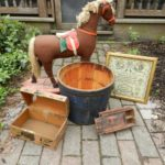 Antique brown rocking horse with cream mane and tail, red saddle, wood bucket, framed sampler, wooden boxes on brick sidewalk