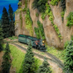 Model train on tracks next to mountainside with evergreens and gray rock cliffs