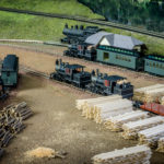 Green model passenger train, two black trains on tracks in yard with stacks of logs and lumber