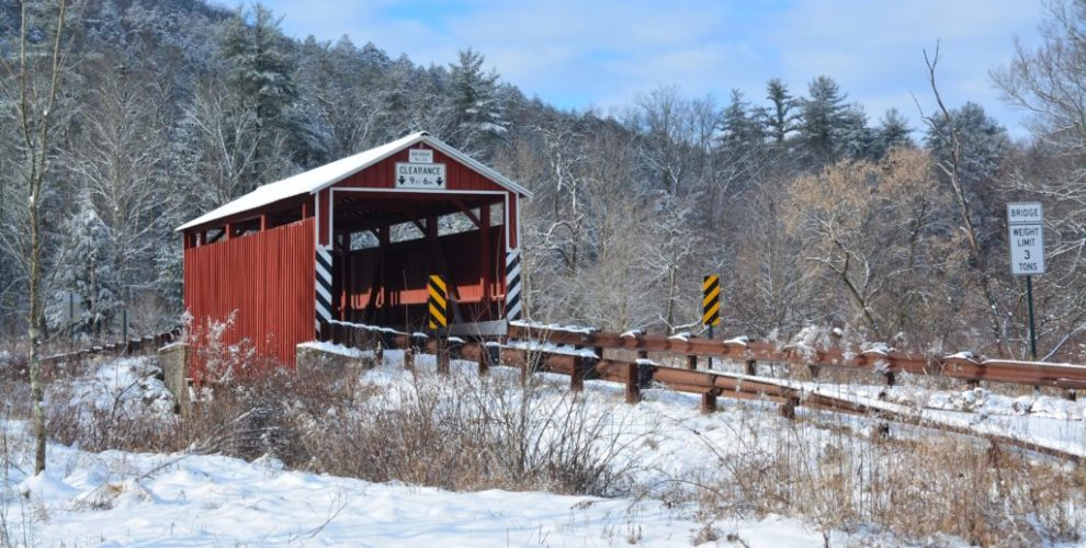 Kramer Covered Bridge - snow covered red bridge with brown wood guardrails on either side of road leading to bridge