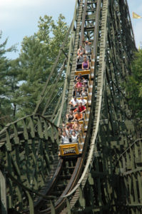People riding down vertical section of wooden roller coaster with green trees in background