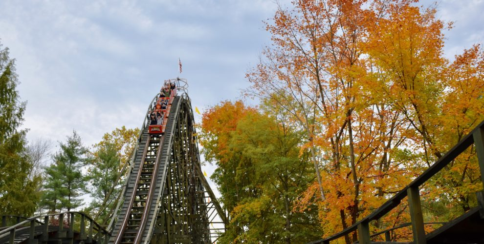 People riding cars on wooden roller coaster surrounded by orange and red trees during fall foliage season