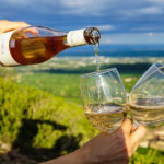 hand holding wine bottle pouring wine into two glasses against background landscape