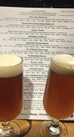 two glasses of golden beer with creamy heads in front of menu