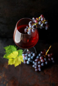 Glass of red wine with grapes by Roberta Sorge https://unsplash.com/@robertasorge